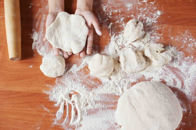 Child holding kneading dough