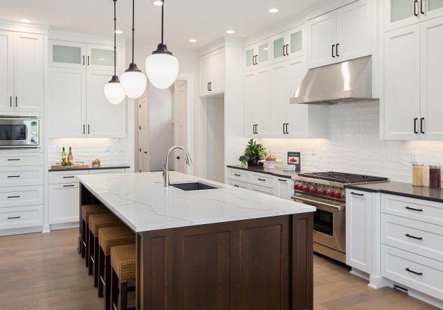 beautiful-kitchen-in-new-luxury-home-with-large-island -pendant-lights -oven -range -and-hardwood-floors.-697394012_4000x2794.jpeg