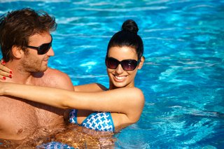 Attractive young couple refreshing in outdoor pool at summertime