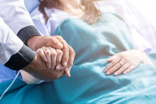 Male doctor holding female patient hand on the hospital bed.